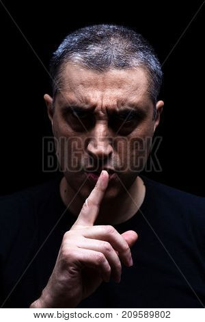Angry mature man with an aggressive look making the silence sign in a threatening and creepy way. Low key, black background. Concept for secret, threat, anger, rage, violence, danger, menace.