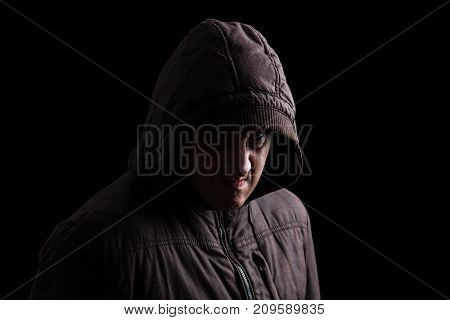 Man with repressed anger and violent instinct hiding in the shadows. Face partly hidden with hood, and standing in the darkness. Low key, black background. Concept for anger, rage, violence, danger