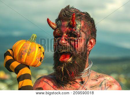 Halloween Devil Man Holding Pumpkin In Striped Sock
