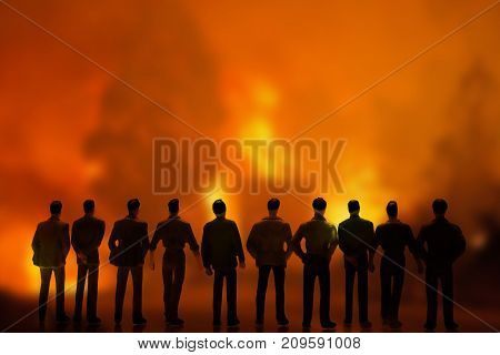 Silhouettes of people watching fire in the forest, conceptual image