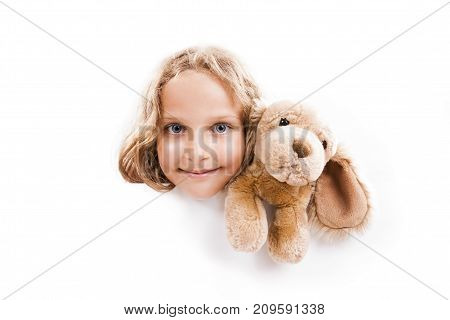 Smiling 7 years old girl with cuddly dog looks out from the empty banner with space for text isolated on white. poster
