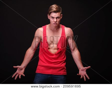 Stressed, angry and strong young man with perfect muscular torso tearing apart a red shirt or stripping on a black background.