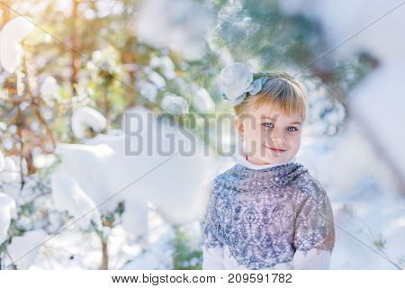 Winter fairy tale. Beautiful little girl is walking in a snowy forest Christmas and new year. Holidays celebration concept.