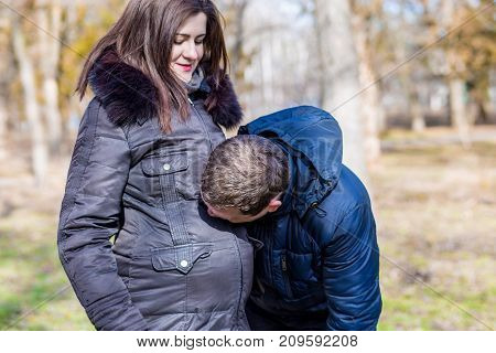 A man kisses the tummy of his beautiful pregnant wife in the autumn park