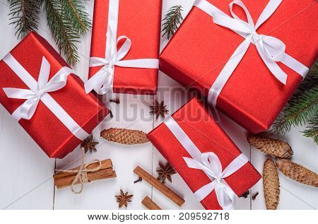 Christmas background with red gift boxes fir tree branches pine cones cinnamon sticks and star anise. Red Christmas gift boxes on white wooden background. Holiday greeting card. Flat lay top view