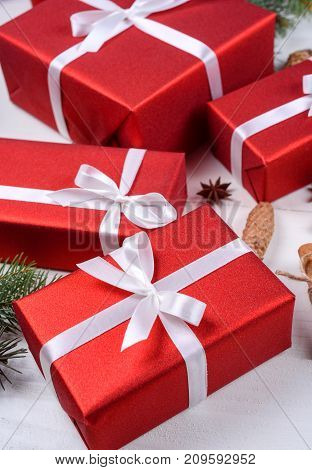 Christmas background with red gift boxes fir tree branches pine cones cinnamon sticks and stars anise. Red Christmas gift boxes on white wooden background. Holiday greeting card