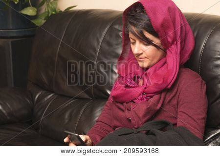 Woman in hijab looking at her phone and text message communicating