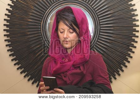 Woman wearing hijab communicating and looking at her phone