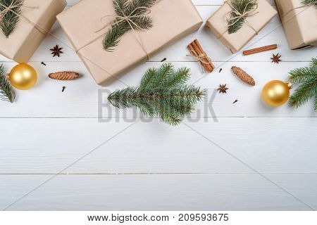 Christmas background with gift boxes wrapped in kraft paper fir tree branches golden glass balls pine cones cinnamon and stars anise on white wooden background free space. Flat lay top view