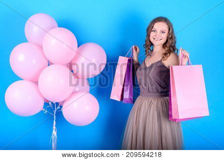 Beautiful young smiling woman holding shopping bags near pink balloons over blue background in black friday holiday free space. Beauty fashion sale concept. Girl on blue background with copy space