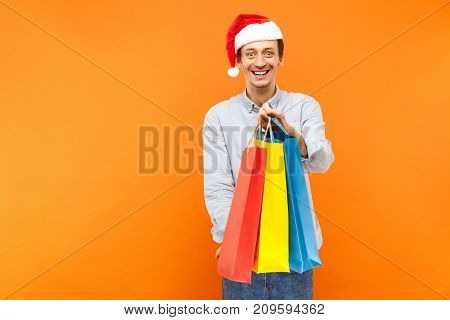 Young Adult Joyful Man In Christmas Red Hat, Toothy Smiling, Showing Colorful Packets At Camera