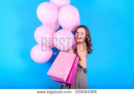 Beautiful young smiling woman in dress holding shopping bags and pink balloons over blue background in black friday holiday free space. Beauty fashion sale concept copy space