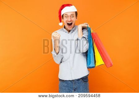 Happiness Success Man Holding Packets, Showing Victory Sign And Looking At Camera With Big Eyes And