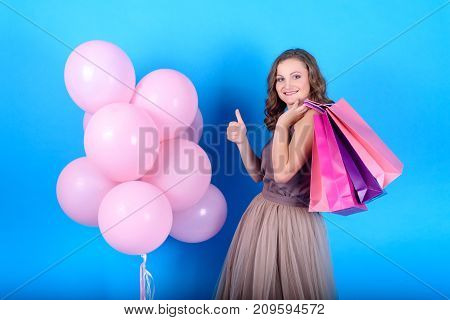Happy young smiling woman in dress holding shopping bags near pink balloons and make her thumb up gesture on blue background in black friday holiday free space. Beauty fashion seasonal sale concept