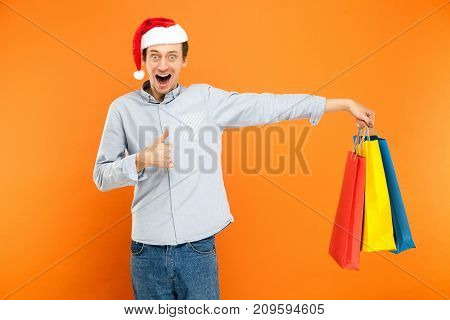 Man In Red Cap, Holding Many Colorful Bags After Christmas Shopping. Thumbs Up And Toothy Smile.