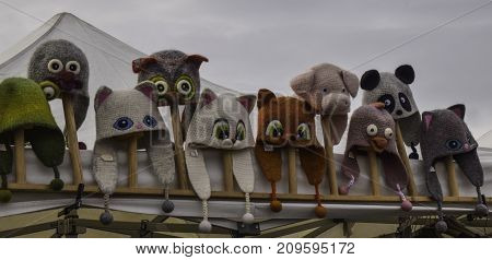 woolen animal shaped children's hats for sale at an outdoor market