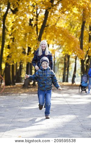 Young Mother and little son in autumn park. Concept of friendly family