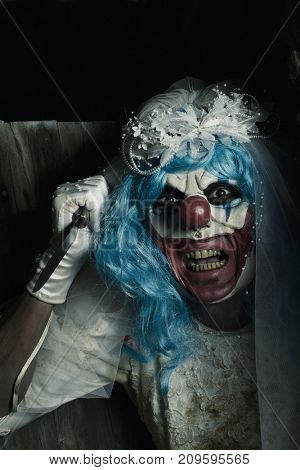 a scary evil clown wearing a dirty and ragged bride dress wields a knife at the door of a creepy house