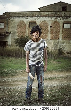 a scary disfigured man with a rusty and bloody cleaver in his hand in front of a house in ruins in a disturbing landscape