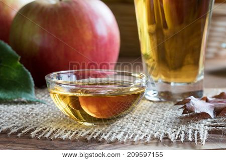 Apple Cider Vinegar In A Glass Bowl, With Apples In The Background