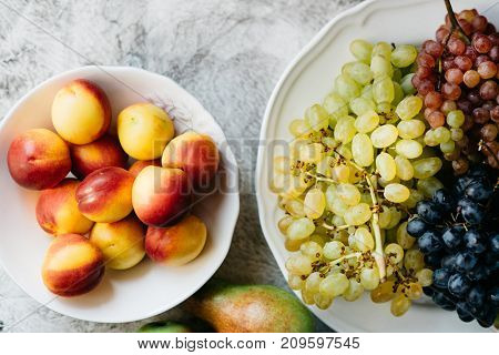 Red and white grape on the plate and white bowl with ripe apricots, view from above