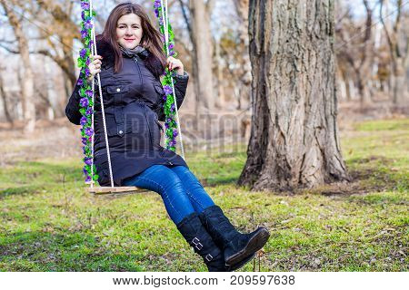 Beautiful pregnant woman touching her belly with hands on the swing in the autumn park
