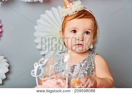Little baby celebrating its first birthday, in front of him cake with candle in the form of 1