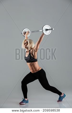 Full length portrait of a confident strong muscular adult sportswoman standing and lifting a barbell isolated over gray background