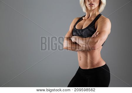 Cropped image of a muscular adult sportswoman standing with arms folded and looking at camera isolated over gray background