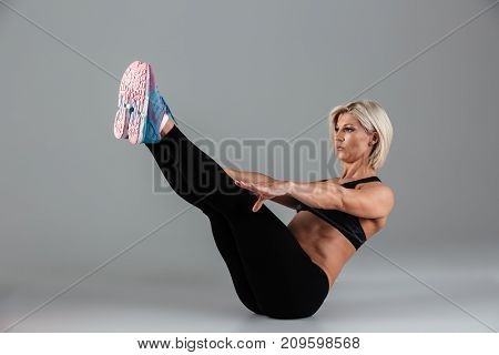 Portrait of a motivated muscular adult sportswoman doing exercises for abs isolated over gray background