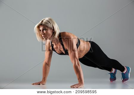 Full length portrait of a motivated muscular adult sportswoman doing push-ups isolated over gray background