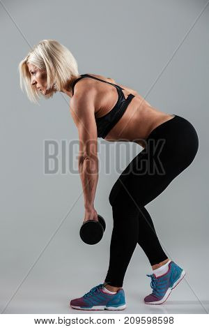 Side view full length portrait of a concentrated muscular adult sportswoman doing exercises with a heavy dumbbell isolated over gray background