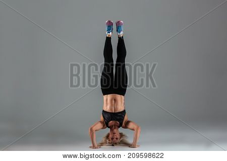 Full length portrait of a muscular adult sportswoman standing upside down isolated over gray background