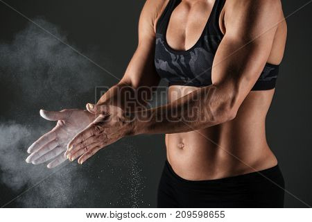 Cropped image of a muscular sportswoman clapping hands with talc powder before work out isolated over gray background
