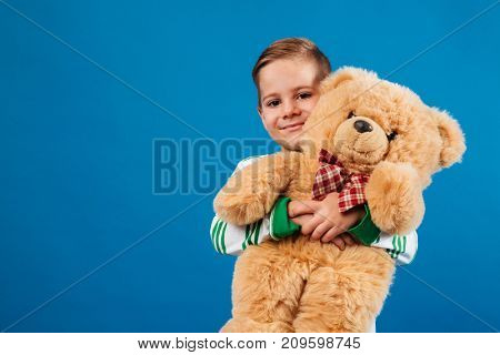 Smiling young boy holding teddy bear and looking at the camera over blue background