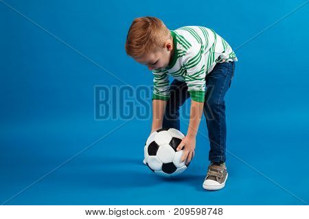 Portrait of a little kid going to kick a soccer ball isolated over blue background