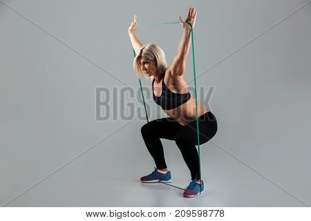 Full length portrait of a serious muscular adult sportswoman working out with a stretching band isolated over gray background
