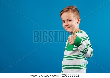 Side view of smiling young boy showing thumb up and looking at the camera over blue background