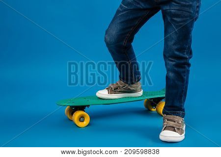 Cropped image of young boy comes on skateboard over blue background