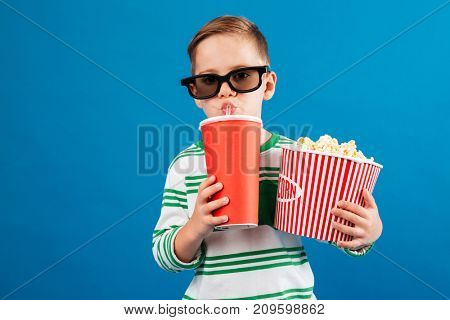 Cool Young boy in eyeglasses preparing to watch the film while drinking soda and holding popcorn over blue background