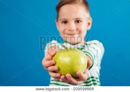 Image of Smiling young boy giving apple at the camera over blue background