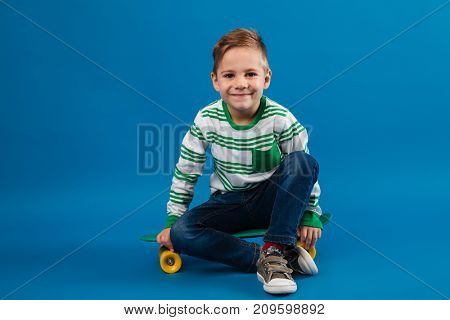 Smiling young boy sitting on skateboard and looking at the camera over blue background