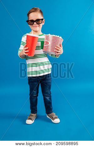 Full length image of Smiling young boy in eyeglasses preparing to watch the film while holding soda and popcorn over blue background