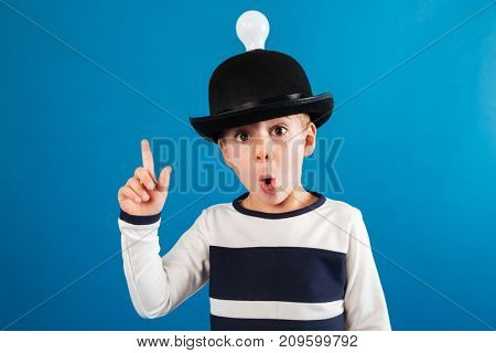 Shocked young boy in hat with lightbulb having idea and looking at the camera over blue background