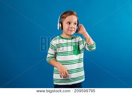 Smiling young boy listening music by headphone and looking aside over blue background