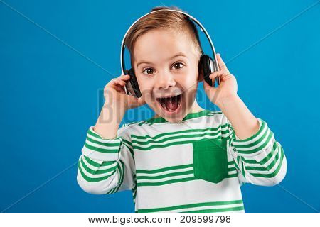 So happy young boy listening music by headphone and looking at the camera with open mouth over blue background
