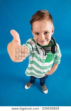 Vertical top view image of happy young boy posing with headphone and showing thumb up at the camera over blue background