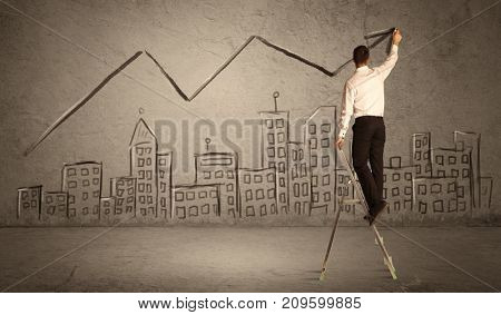 A man in elegant suit standing on a small ladder and drawing a line on brown wall background with buildings