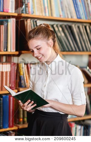 Portrait of a young girl in a white blouse who is reading a book in the library. Close-up. The concept of education.