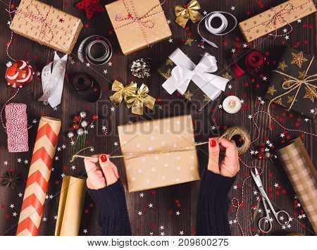 Woman hand tying bow with twine for packaging christmas gift box. Process of package new year gift box. Christmas packaging wrapping paper ribbon twine bow and thread scissors balls on wooden background